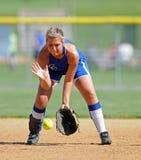 fielding софтбол мяч, посланный по земле девушок Стоковая Фотография
