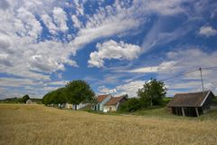 Fields against a blue sky. Showing an interesting cloudscape. A street with small house can be seen in the distance Stock Photos