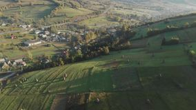 Fields in the Carpathian Mountains. Hay Harvest. Ukraine. Aerial View Of The Landscape With Small Village In Mountains, Highway Through the Village in the stock video footage