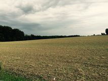 Fields in the countryside. Here we have a magnificent freshly cut field and guarded by a nearby forest, under a rather threatening sky Royalty Free Stock Photo