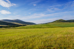 Fields and low mountains of Khakassia. Fields and meadows in the low mountains. Clear sunny summer day. Khakassia. Summer 2014. Siberia Stock Photos