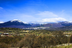 Fields, mountains and blue sky. Landscape with green fields, a village, snow mountains and a blue sky Stock Image