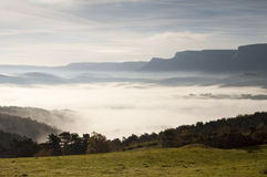 Fields and mountains on a cold morning, fog in the valley and clouds in the sky Stock Photo