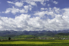 Fields and mountains. Splendid mountains,beautiful fields,blue sky and clouds form a paradise on earth.the small village  is the place where people are longing Stock Photo