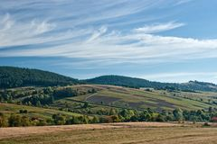 Fields and pastures. Hills with fields and pastures under blue sky with stratus clouds Stock Photography