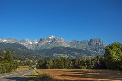 Fields, road, forest, alpine landscape and blue sky in Saint-Gervais-Les-Bains. Fields, road, forest, alpine landscape and blue sky in the background, Saint royalty free stock photography