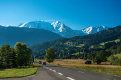 Fields, road, forest, alpine landscape and blue sky in Saint-Gervais-Les-Bains. Fields, road, forest, alpine landscape and blue sky in the background, Saint royalty free stock image