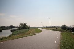 Fields, roads,bicycle lanes and canals along the of the Hollandsche IJssel in Moordrecht, the Netherlands. Fields, roads,bicycle lanes and canals along the of royalty free stock photos