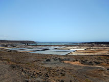 The fields for salt mining on the banks of the Atlantic Ocean. Blue horizon, turquoise water. Stock Photo