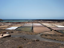 The fields for salt mining on the banks of the Atlantic Ocean. Blue horizon, turquoise water. Lanzarote Stock Image