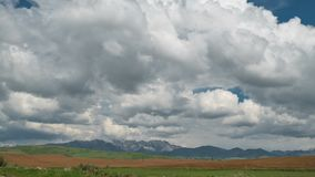 Fields and storm clouds over mountains. Timelapse 4K. UltraHD stock video footage