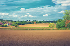 Fields at sunny afternoon. Beautiful afternoon landscape with plowed fields on hills and houses in the background under cloudy sky royalty free stock images