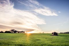 Fields at sunset with a little house stock photos