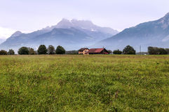 Fields in the swiss Alps. In a valley, in the background are mountains with snow on a cloudy day Royalty Free Stock Photo