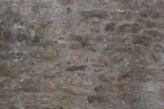 Fieldstone wall with various colored chunks of sandstone. Weathered fieldstone wall with variously colored sandstone, with moss and a few other small plants Royalty Free Stock Image
