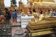 Fieles en Wat Phra That Doi Suthep que circunda el Chedi con reforrar la estatua de Buda en primero plano foto de archivo libre de regalías