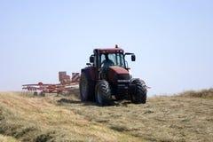 Fienagione: fieno di giro del trattore. Immagini Stock Libere da Diritti