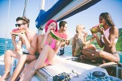 Fiends που έχουν τη διασκέδαση σε μια βάρκα πανιών και που τρώνε το καρπούζι Στοκ Εικόνες