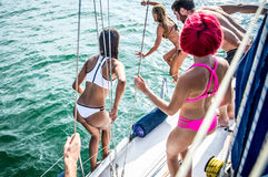 Fiends having fun on a sail boat and jump in the water Stock Photo