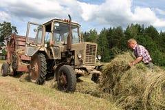 Fieno di tempo di raccolto, trattore-driver russo dell'agricoltore che lavora nel hayfi Fotografia Stock