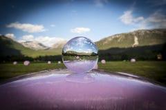 Fieno-palle rosa sotto un cielo blu profondo visto attraverso una sfera di cristallo immagine stock