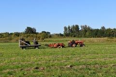 Fieno pressato con la sassola, il vagone ed il trattore Fotografia Stock Libera da Diritti