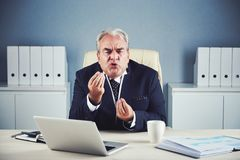 Fierce angry mature businessman explaining using hands. Furious mad elderly male in business suit sitting at office workplace with laptop emotionally criticizing royalty free stock images
