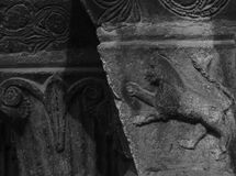Fierce animal lion on the capital. Shot in black and white, detail on the sculpture on the facade of this historic building church representing some characters royalty free stock photography