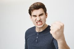 Fierce confident stylish european dark-haired male with trendy haircut holding fist in front of him as if ready for. Fierce and confident stylish european dark Royalty Free Stock Image