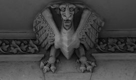 Fierce dragon standing on the main entrance. Shot in black and white on the sculpture on the facade of this historic building representing some characters / stock photo