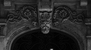 Fierce flower creature on the main door. Shot in black and white, detail on the sculpture on the facade of this historic building representing some characters stock photos