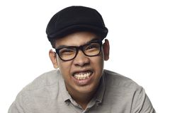 Fierce grinning malay man. Fierce malay man showing gritted teeth wearing black cap and spectacles with white background royalty free stock photo