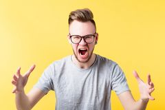 Fierce irritated emotional hipster guy portrait. Portrait of fierce hipster guy on yellow background. Yelling young emotional man in glasses. Irritated facial stock images