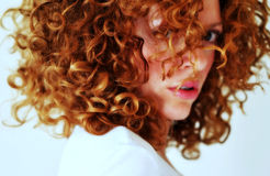 Fierce mixed young woman with curly red hair stock photos