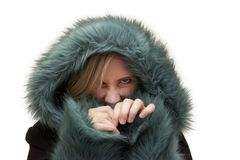 Fierce model in green fur hides and snarls. Beautiful blond woman in studio has a green fur hood pulled up and is hiding and making angry face stock photo