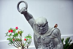 Fierce statue and a little bird Stock Image