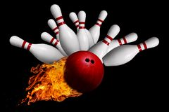Fiery Ball Hitting Pins in Bowling Strike Isolated on Black Back. Fiery red bowling ball striking against pins in a ten-pin bowling game. Isolated on black Royalty Free Stock Photography