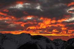 Fiery Banff sunset. Brilliant fiery orange autumn sunset on the clouds over the mountains from gondola in Banff, Alberta royalty free stock image