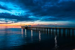 Fiery cloud and sky over the sea at sunset with a pier. Fiery cloud and sky over the sea at sunset stock photo