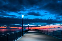 Fiery cloud and sky over the sea at sunset. With a pier stock images