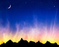 Fiery Clouds and Stars. Fiery clouds at sunset with the moon and stars against a mountain silhouette Royalty Free Stock Photos