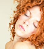 Fiery Curls. Young woman with fiery, red curls Stock Photo