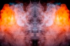 A fiery drawing of evaporating vapus smoke on a black background awe-inspiring a drawn head of a mystical creature in flames of. Yellow orange and red royalty free stock images