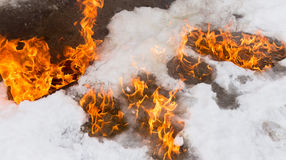 Fiery flame on the white snow in winter Stock Photo