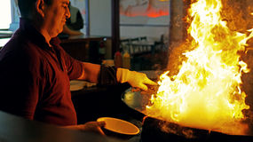 Fiery Grill. A cook at a Mongolian Grill restaurant in Portland, Oregon is cooking on the giant wok while the food is being engulfed by fire Royalty Free Stock Photos