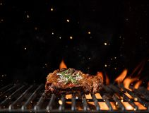 Fiery grill grid with piece of beef steak. Royalty Free Stock Photo