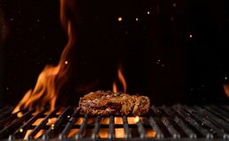 Fiery grill grid with piece of beef steak. Royalty Free Stock Images