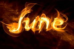 Fiery letters of the word June. On a black background Royalty Free Stock Images