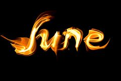 Fiery letters of the word June. On a black background Royalty Free Stock Image