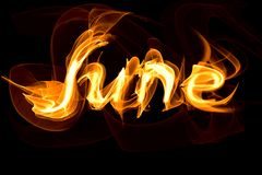Fiery letters of the word June. On a black background Royalty Free Stock Photography